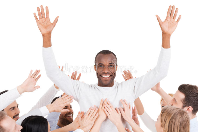 They chose their leader. Happy young African men standing against white background and keeping arms outstretched while group of excited people stretching hands royalty free stock images