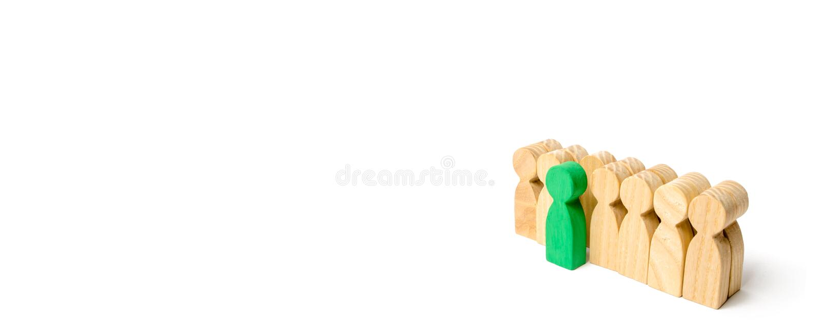 The chosen person among others. A human figure of green color st. Ands out from the crowd. Wooden figures of people. A talented worker, a successful choice royalty free stock photo