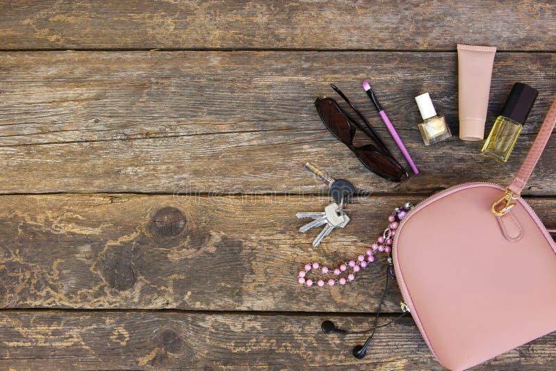 Choses de bourse ouverte de dame Les cosmétiques et les accessoires des femmes sont tombés hors du sac à main image stock