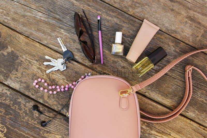 Choses de bourse ouverte de dame Les cosmétiques et les accessoires des femmes sont tombés hors du sac à main photo libre de droits