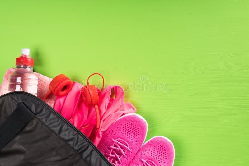 Choses pour le sport et une bouteille de l'eau dans un sac noir sur le coin d'un fond vert de conseil images libres de droits