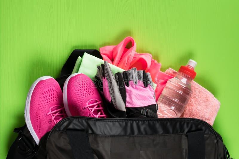 Choses roses pour le sport et une bouteille de l'eau dans un sac noir sur un conseil vert photo stock