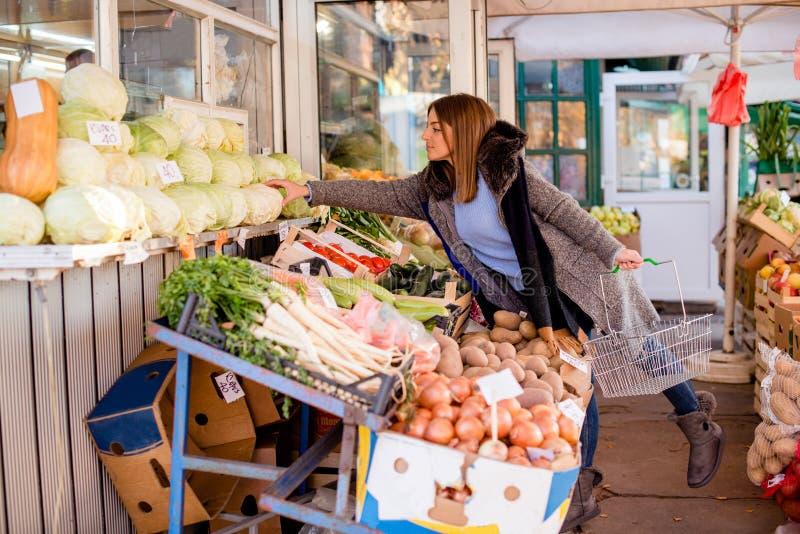 Chou de cueillette de jeune femme au marché du ` s d'agriculteur photographie stock libre de droits
