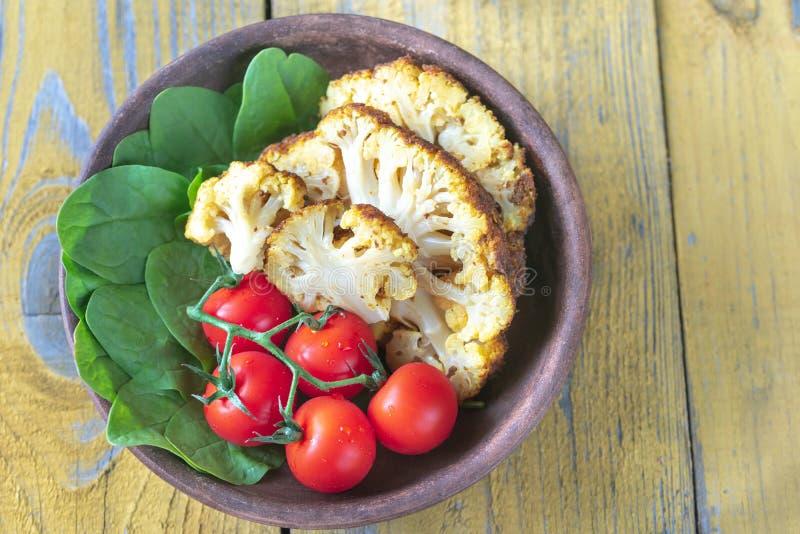 Chou-fleur cuit au four avec des tomates-cerises et des épinards frais photo stock