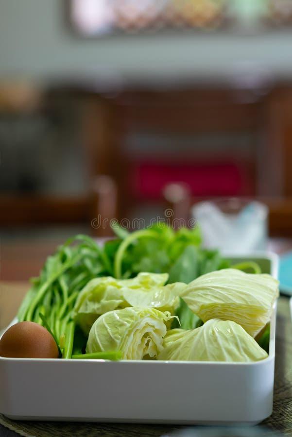 Chou frais, gloire de matin fra?che et oeufs dans un plateau blanc pour un ensemble japonais de Shabu images stock