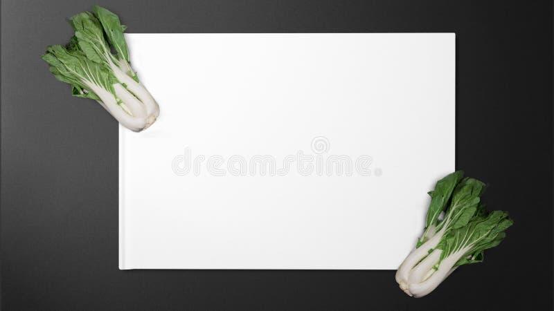 Chou frais sur le livre blanc sur le fond noir photos libres de droits