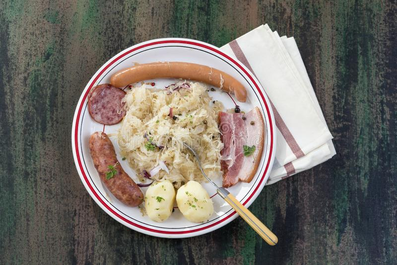 Choucroute garnie,一块典型的alsacian板材,用香肠、烟肉、德国泡菜和土豆在木背景 免版税库存照片