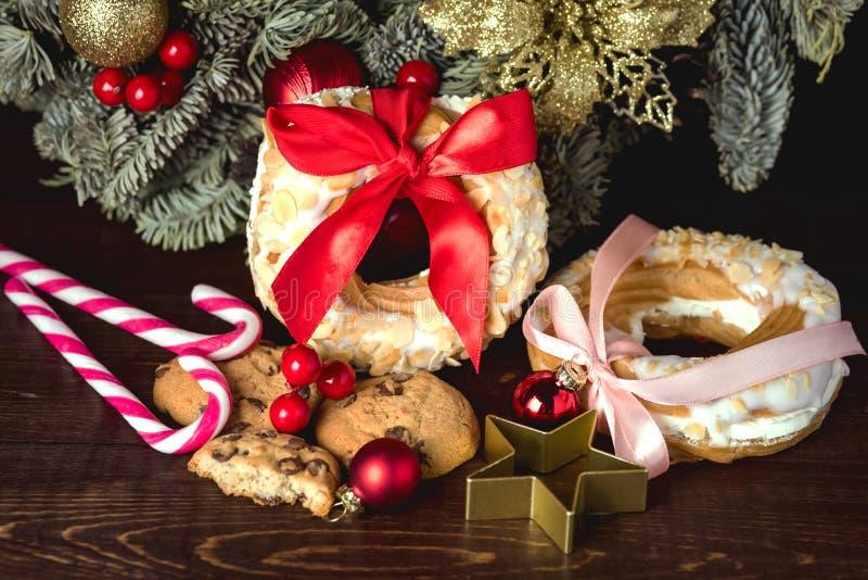 Choux печенье и печенья колец слойки сливк на венке рождества тросточки конфеты концепции еды рождества деревянной предпосылки пр стоковая фотография