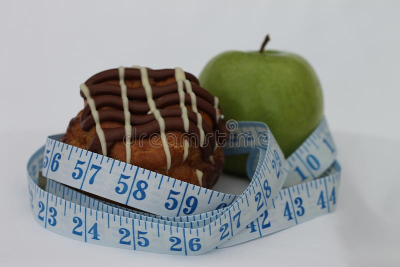 A choux bun and green apple stock photos
