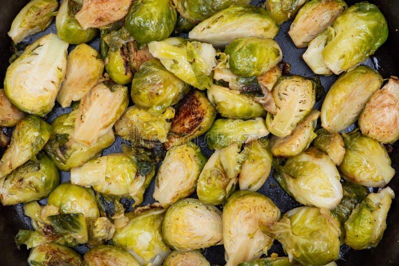 Choux de bruxelles organiques rôtis dans une poêle de fonte comme le fond photographie stock
