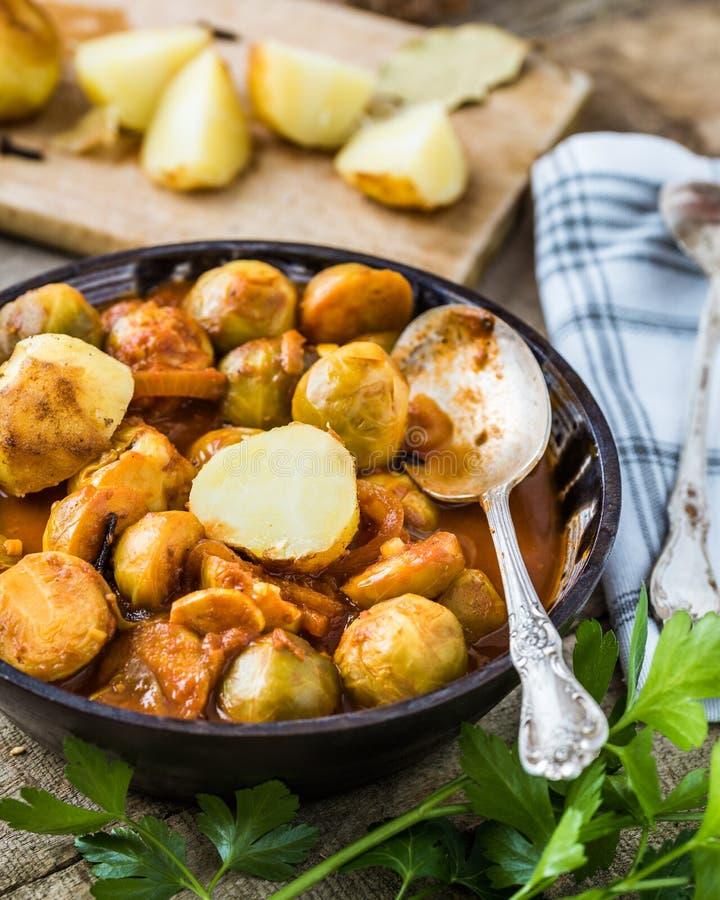 Choux de Bruxelles rôtis avec des pommes de terre dans la cuvette en céramique faite maison photographie stock