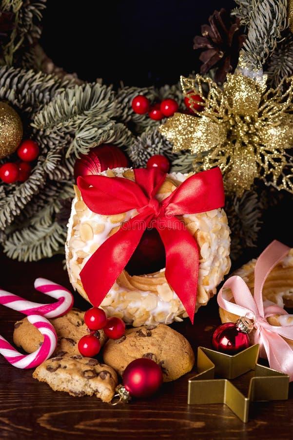 Choux pastelaria e cookies dos anéis do sopro de creme em doces festivos Cane Christmas Wreath do conceito do alimento do Natal d fotos de stock