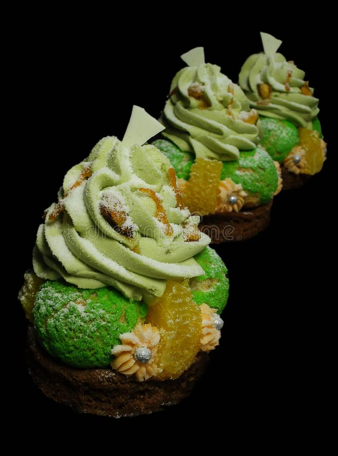 Choux pastry desserts with oranges, pistachio ganache and white chocolate decorations. Orange chocolate tarts with black french macarons and persimmon on black royalty free stock images