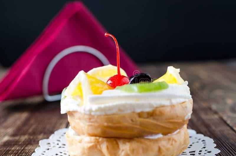 Chouxgebakje met fruit op een houten achtergrond royalty-vrije stock afbeelding
