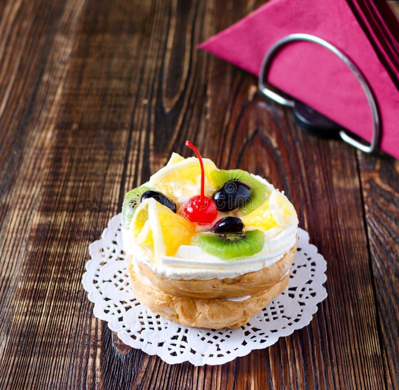 Chouxgebakje met fruit op een houten achtergrond stock foto
