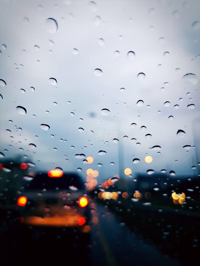 Chova a gota no vidro com o carro na estrada fotografia de stock