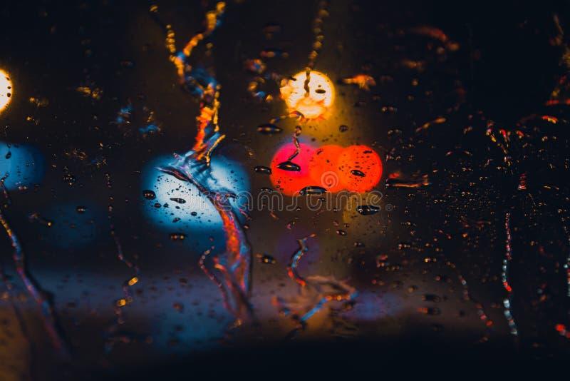 Chova gotas na janela com o bokeh da luz da estrada que chove a estação foto de stock royalty free