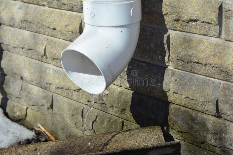 Chova a tubulação do downspout da calha para a drenagem da água do telhado e a parede waterproofing da fundação da casa imagem de stock