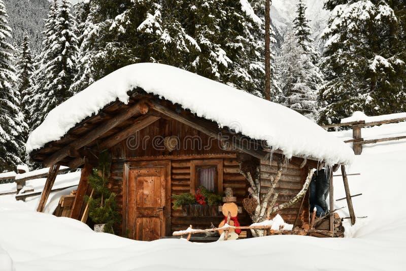 Choza alpina en invierno en las montañas Paisaje del invierno en un bosque cerca del lago Antholz Anterselva, el Tirol del sur foto de archivo