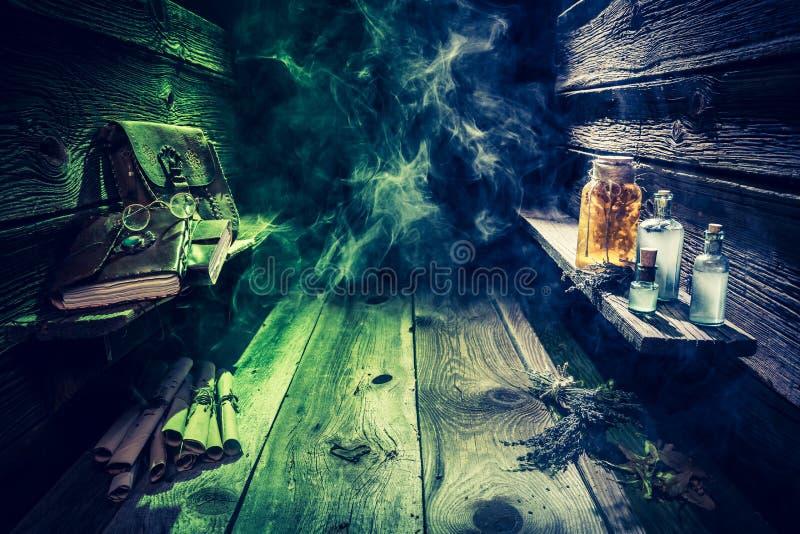Choza de la bruja con las pociones, las volutas, los libros y el humo azul, verde con el espacio de la copia para Halloween imágenes de archivo libres de regalías