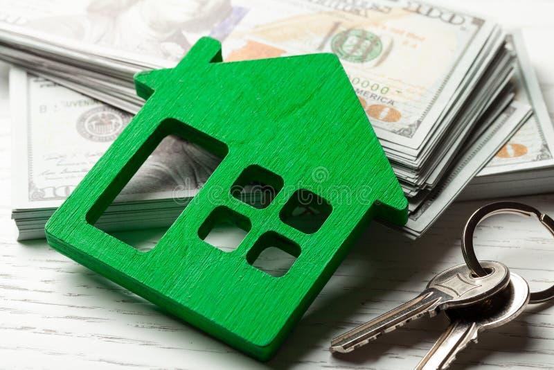 Choza de madera con el dinero y llaves en un fondo blanco Compra o alquiler o venta Remont o seguro del concepto para la casa fotografía de archivo