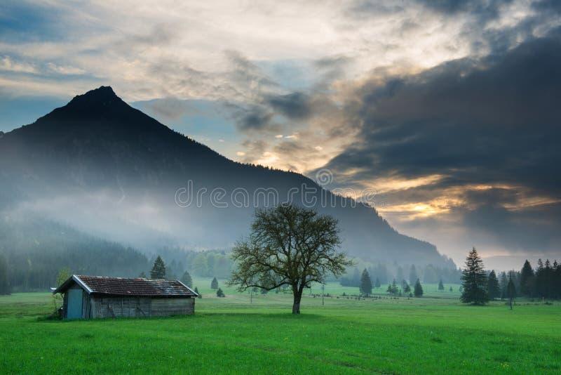 Choza de madera en el humor de la puesta del sol en el prado de la montaña fotos de archivo libres de regalías