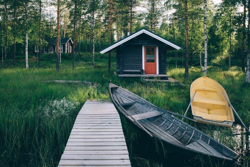 Choza de madera tradicional Sauna finlandesa en el lago y el embarcadero con los barcos de pesca fotos de archivo libres de regalías