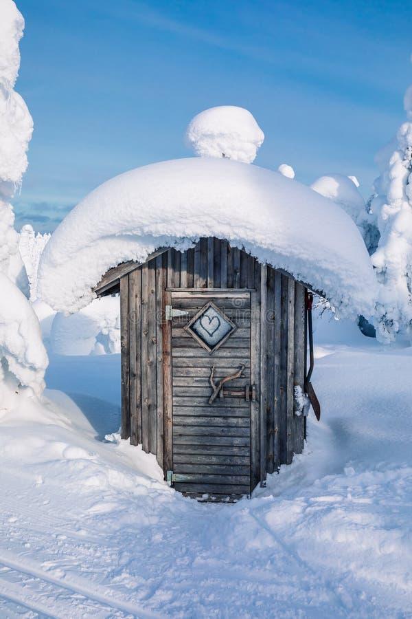 Choza de madera vieja en bosque nevoso del invierno en Finlandia, Laponia imagen de archivo libre de regalías