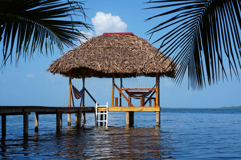 Choza de Palapa con el tejado cubierto con paja sobre el mar del Caribe fotos de archivo