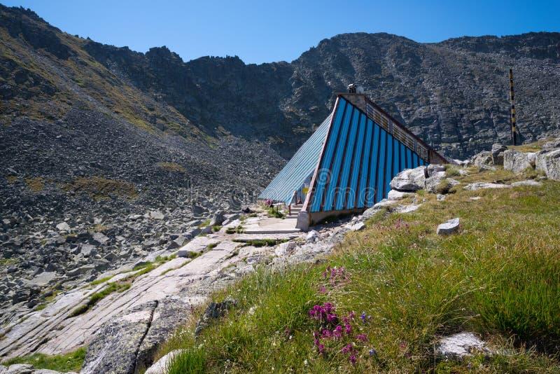 Choza del refugio de la emergencia a lo largo de una pista de senderismo en la montaña fotografía de archivo