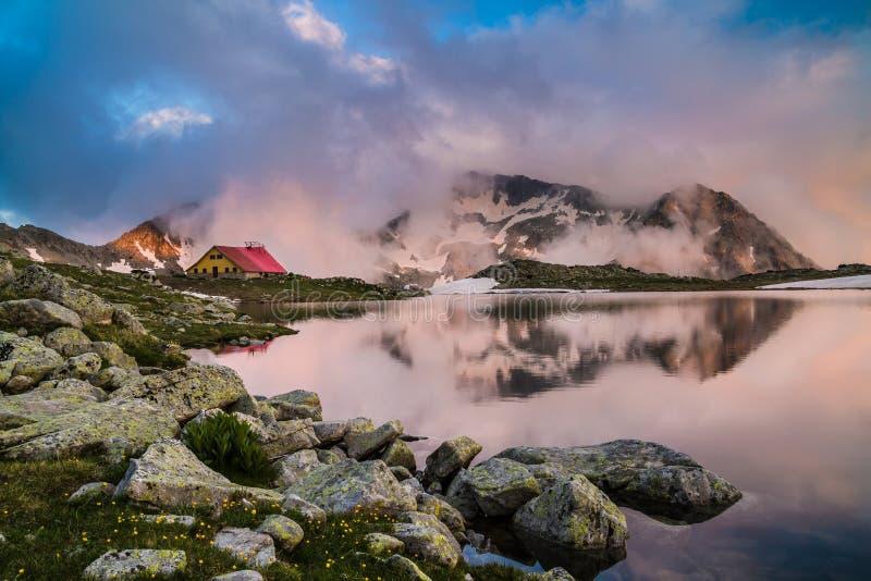 Choza en alta montaña con el lago imagenes de archivo