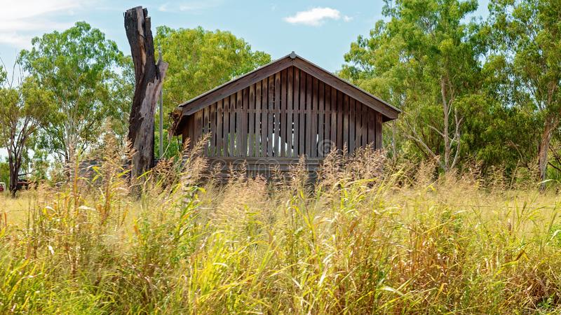 Choza vieja abandonada de la madera afrontada por la hierba alta foto de archivo libre de regalías