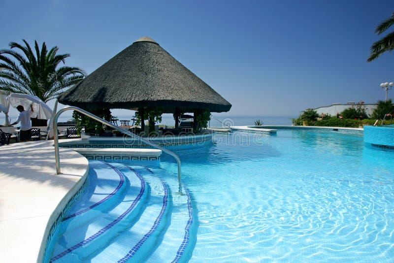 Choza y barra de Tiki por la piscina del hotel de lujo foto de archivo