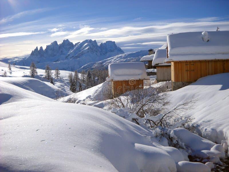 Chozas alpinas debajo de la nieve fotos de archivo