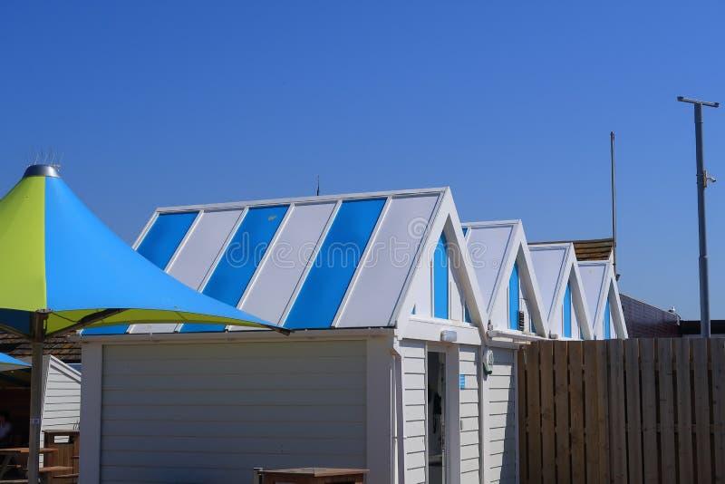 Chozas azules y blancas de la playa y paraguas coloridos fotografía de archivo