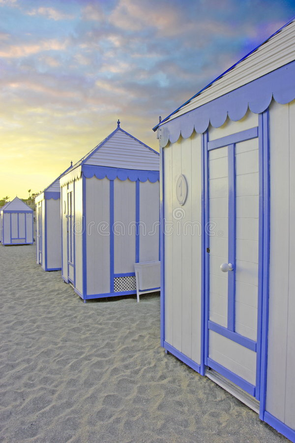 Chozas de la playa en la puesta del sol fotos de archivo