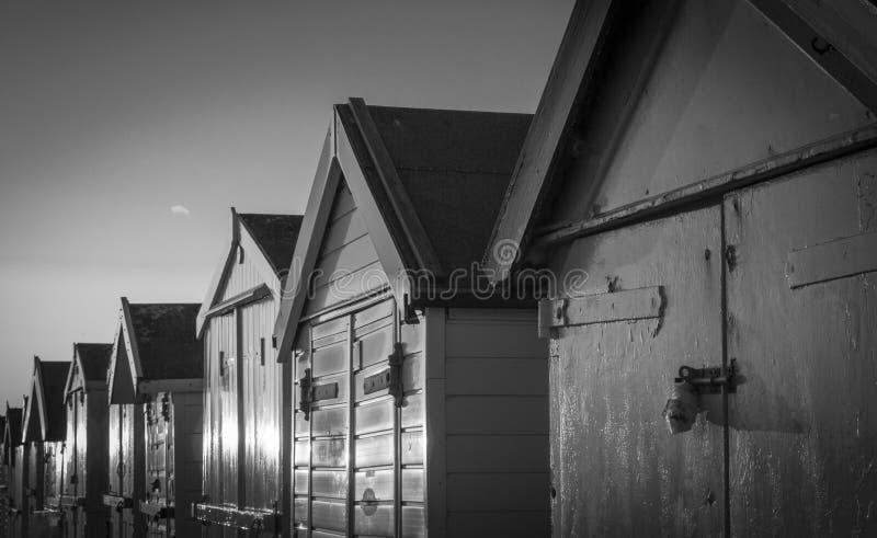 Chozas de la playa en la puesta del sol en blanco y negro fotos de archivo libres de regalías