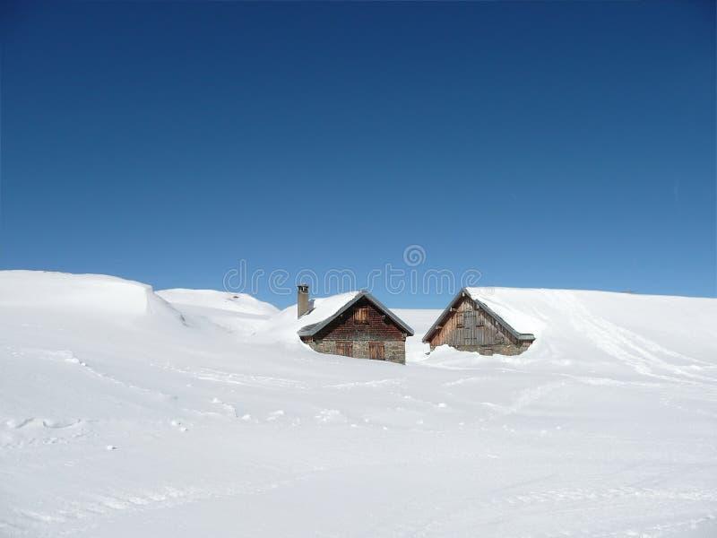 Chozas en nieve profunda en las montañas con el copia-espacio foto de archivo