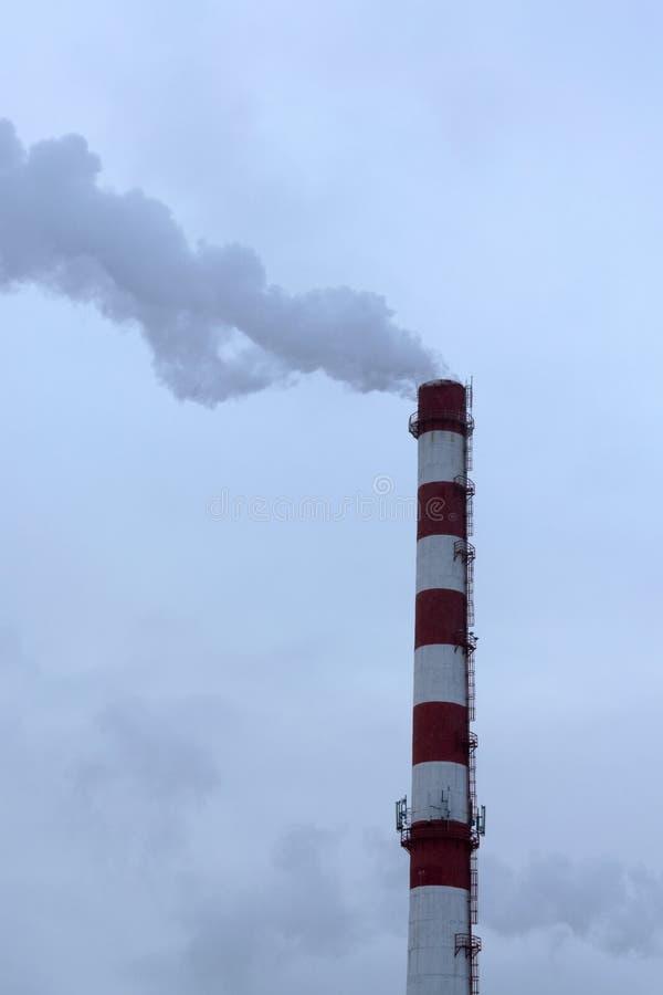CHP alto da tubulação no fundo do céu azul, névoa, poluição atmosférica foto de stock