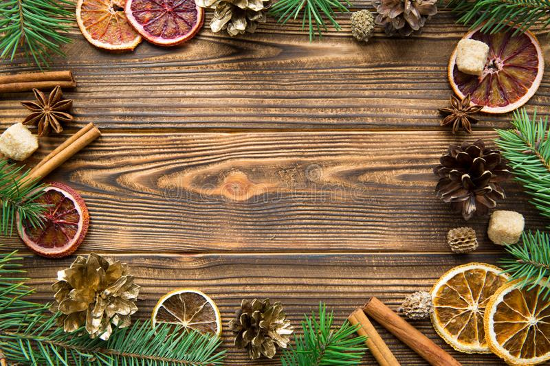 Chrismas holiday brown background. Dried sicilian oranges with cinnamon sticks, anise and golden cones. Copy space royalty free stock photo