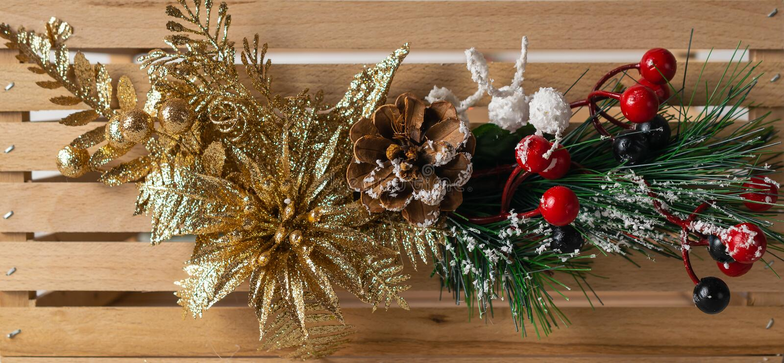 Chrismas sparkling decorative banner on wooden background with fir tree branches and golden flower stock image