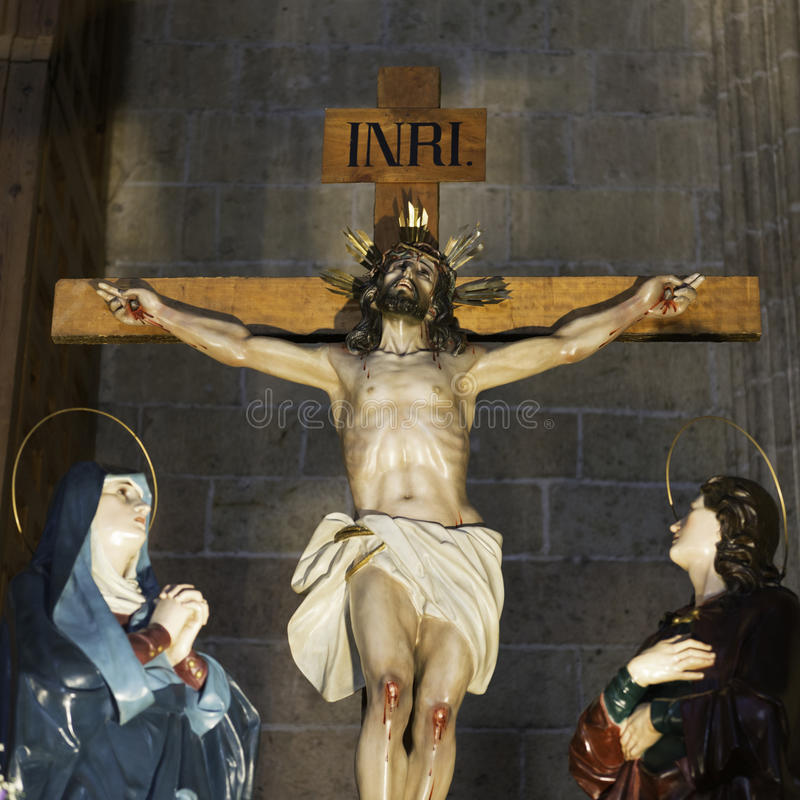 Christ on the Cross. Wooden sculpture showing Jesus on the cross from head to knees, with defocused Virgin Mary and San Juan. Located in the chapel of San Andres stock images