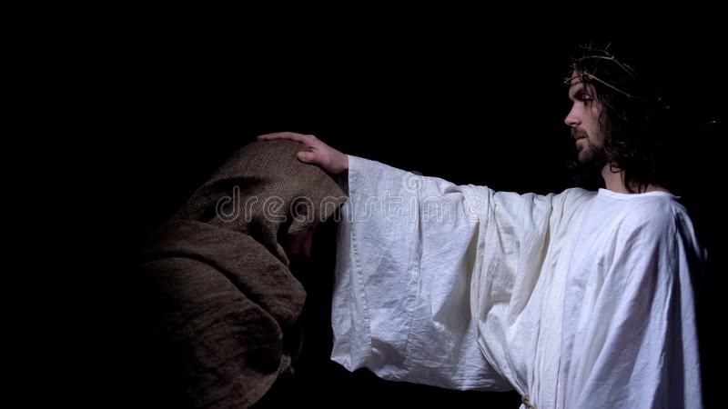 Christ in crown of thorns blessing poor man, forgiving sins after confession. Stock photo stock image