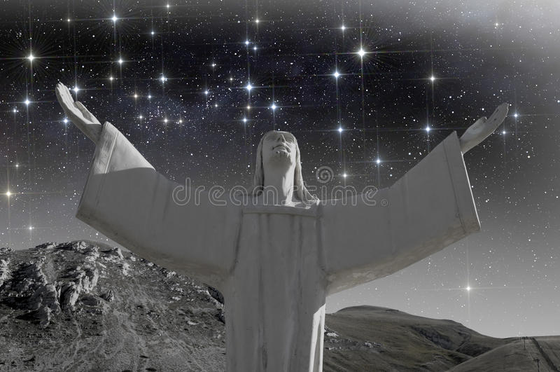 Christ with open arms under starry sky stock photography