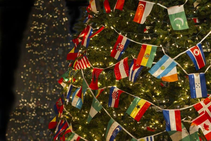 Christas-Baum mit Vielzahl-Landesflaggen, die Welt vereinigt und Frieden wünschend lizenzfreie stockfotografie