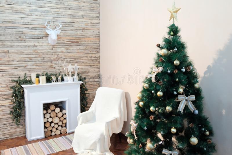 Christbaumständer nahe dem Nachttisch und dem Kamin gegen die weiße Wand Thema-guten Rutsch ins Neue Jahr Papierrotwild hängendes stockfotos