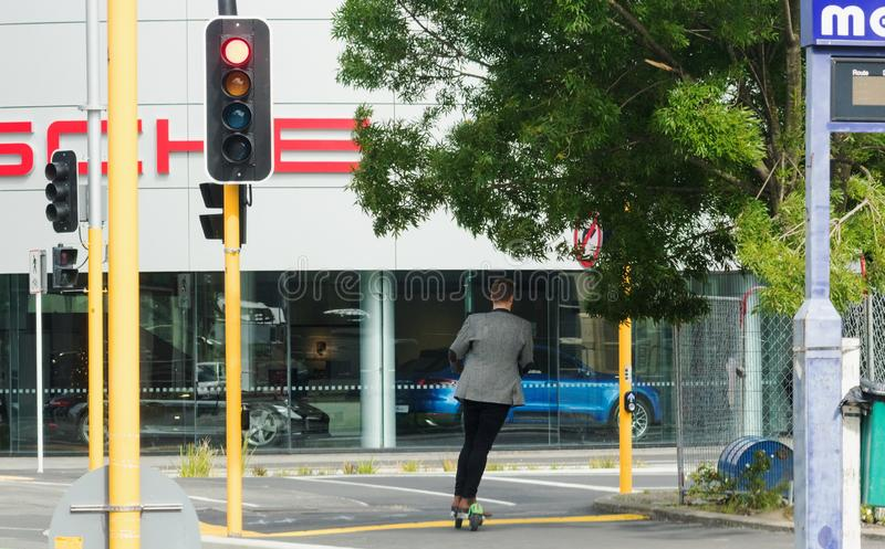 A young man scoots around town on an electric Lime Scooter. Christchurch, New Zealand - 1 December 2018: A young man scoots around town on an electric Lime stock images