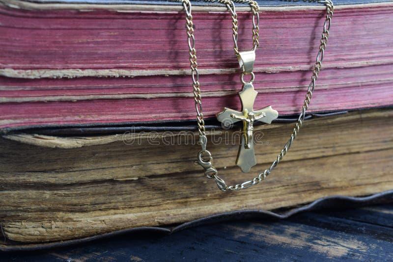 Christelijk kruis met de oude heilige Bijbel op de lijst stock foto's