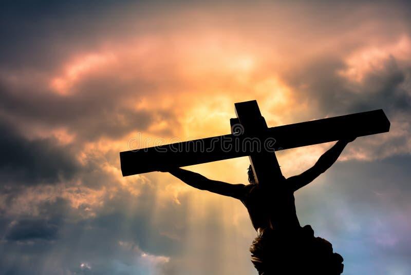 Christelijk kruis met Jesus Christ-standbeeld over stormachtige wolken stock afbeeldingen