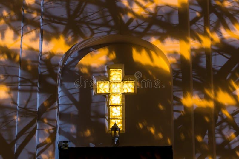 Christelijk kruis op de voorgevel van de kerk bij nacht stock foto